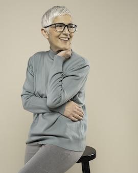 Dorosła kobieta z krótkimi siwymi włosami i okularami, ubrana w golf i pozująca w studio