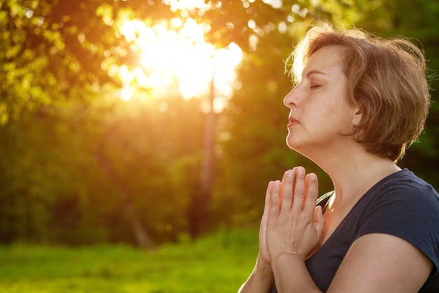 Dorosła kobieta z krótkimi włosami medytuje ze złożonymi dłońmi w parku z zamkniętymi oczami w promieniach masywnego słońca latem