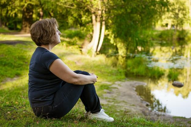 Dorosła kobieta z krótkimi włosami siedzi w ciemnej sukience w parku na trawie w promieniach zachodzącego słońca letniego dnia