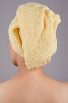 Dorosła kobieta z nagimi plecami, widok z tyłu. nad szarą ścianą. koncepcja pielęgnacji skóry ciała. izoluj na szarej ścianie