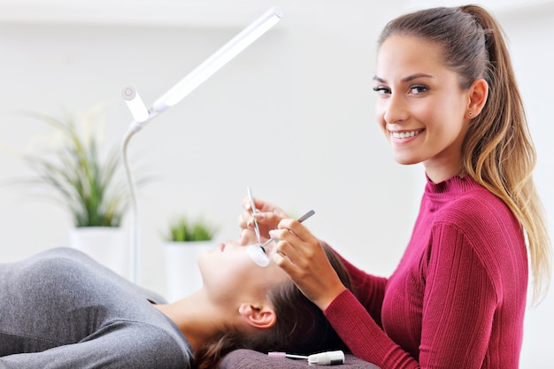 Dorosła kobieta z przedłużaniem rzęs w profesjonalnym salonie kosmetycznym
