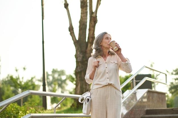 Dorosła kobieta z torebką pijąca kawę w parku