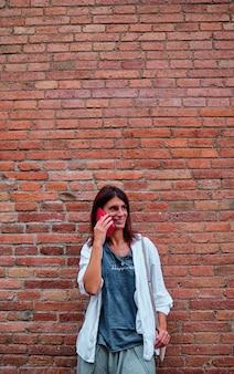 Dorosła kobieta za pomocą telefonu komórkowego z murem za
