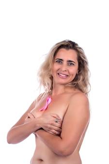 Dorosła kobieta zakrywająca piersi rękami różową wstążką świadomości raka piersi, na białym.