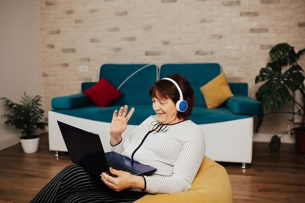 Dorosła kobieta ze słuchawkami siedzi na żółtym fotelu w salonie nawiązuje połączenie wideo