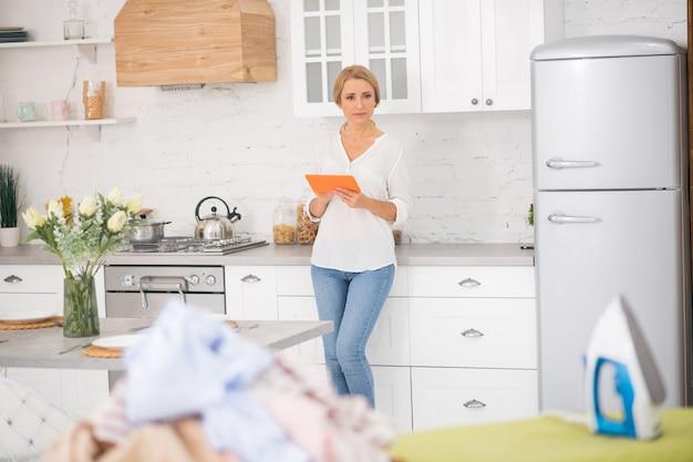 Dorosła ładna kobieta w dżinsach z tabletem w dłoniach stojąc w domu w kuchni