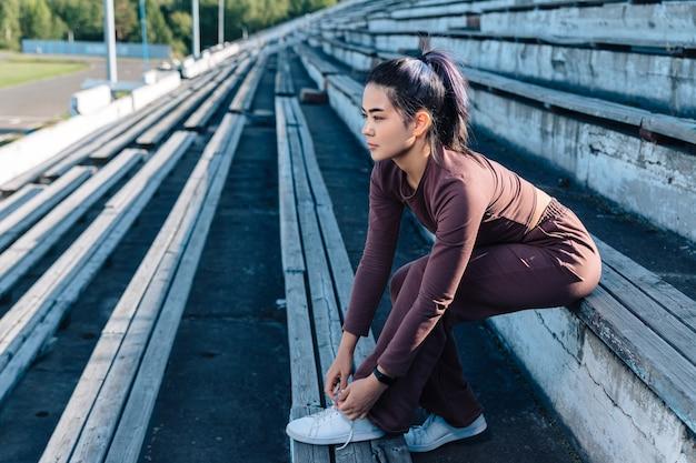 Dorosła młoda dziewczyna o azjatyckim wyglądzie w fioletowym dresie siedzi na drewnianej ławce, odwraca wzrok i zawiązuje koronkę.