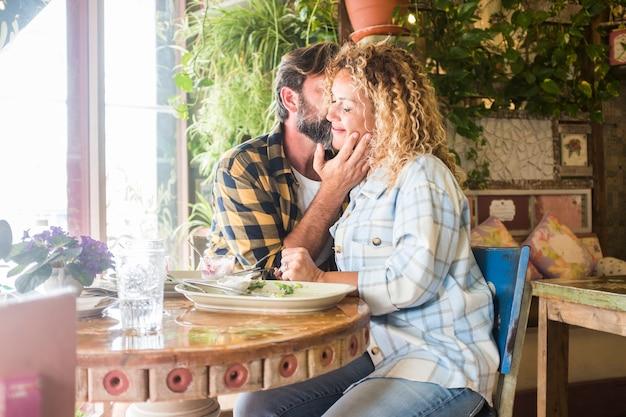Dorosła młoda para kaukaska w emocjach miłości i czułości siedzi razem w restauracji ciesząc się związkiem - randki z dojrzałymi ludźmi, całowanie i zabawa podczas lunchu w barze