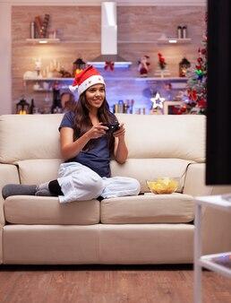 Dorosła osoba odpoczywająca na sofie w świątecznej udekorowanej kuchni, grająca w gry wideo online