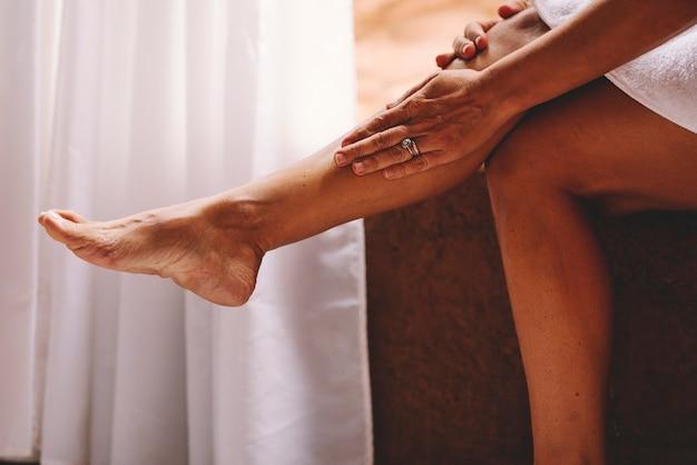 Dorosła pani nakłada krem do pielęgnacji skóry na nogę do leczenia przeciwstarzeniowego kobiety w domu w b