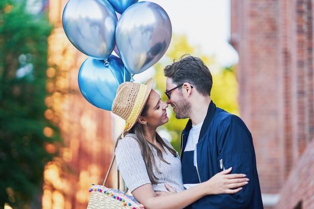 Dorosła para całuje się na spacerze po mieście, trzymając balony