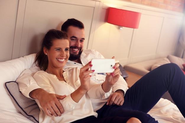 Dorosła para leżąca na łóżku hotelowym ze smartfonem