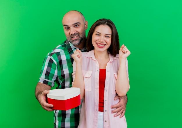 Dorosła para pod wrażeniem mężczyzny trzymającego pudełko w kształcie serca kładąc rękę na talii kobiety uśmiechnięta kobieta zaciskająca pięści