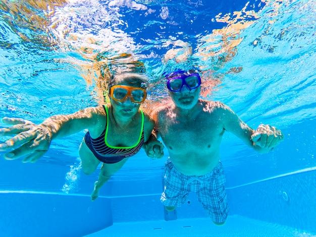 Dorosła para starszych osób dobrze się bawi, pływając w basenie pod wodą z kolorowymi zabawnymi maskami do nurkowania, koncepcją nurkowania i aktywnym emerytowanym mężczyzną i kobietą, ciesząc się stylem życia niebieska woda kaukaski dorośli