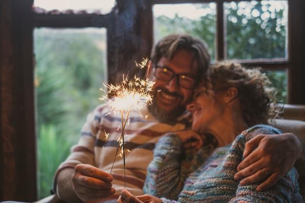 Dorosła para trzyma błyszczące światło i świętuje w domu