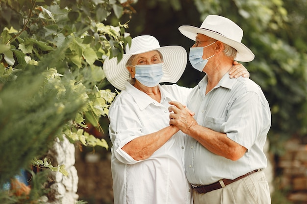 Dorosła para w letnim ogrodzie. motyw coromavirus. ludzie w masce medycznej. przystojny starszy w białej koszuli.