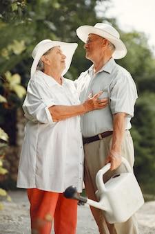 Dorosła para w letnim ogrodzie. przystojny starszy w białej koszuli. kobieta w kapeluszu. rodzinne podlewanie.