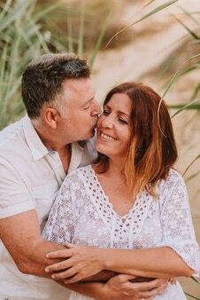 Dorosła para w połowie przytulanie i całowanie, ubrana w białe sukienki na wydmie plaży podczas zachodu słońca