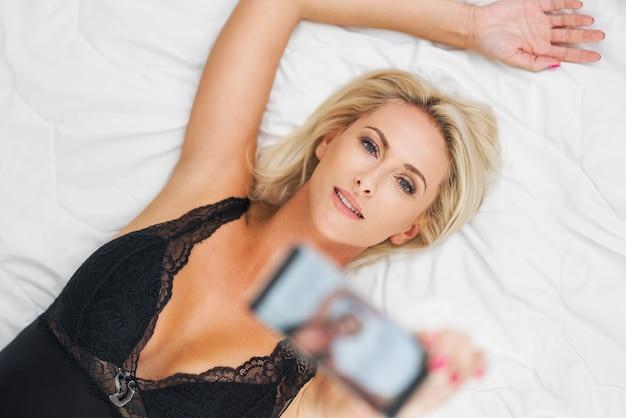 Dorosła piękna kobieta budzi się w pełni wypoczęta i używa smartfona