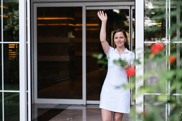 Dorosła piękna kobieta w białej sukni macha do kogoś, sąsiada lub gościa kawiarni stojącego w drzwiach. przyjazny uśmiech na twarzy, lato i kwiaty. spotkanie lub rozstanie