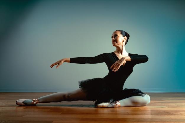 Dorosła piękna kobieta w wieku 45-55 lat, balerina w pointe butach siedzi na podłodze i pozuje do aparatu