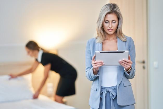 Dorosła pokojówka i kierownik hotelu sprzątają pokój
