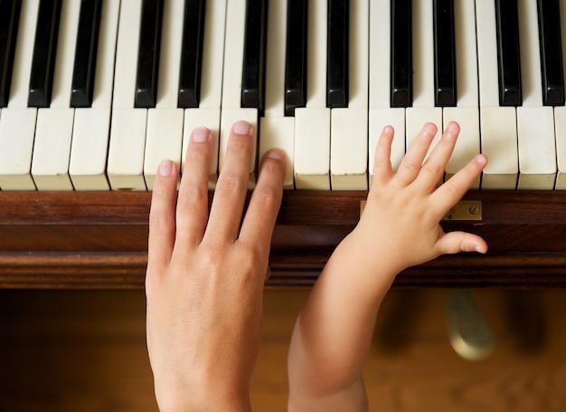 Dorosła ręka bawić się pianino z dziecko ręką