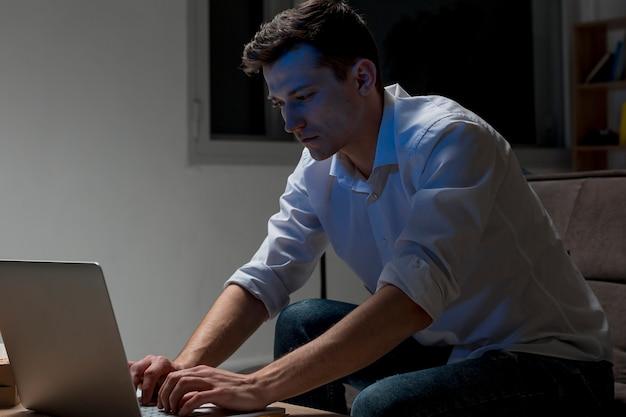 Dorosła samiec pracuje na laptopie przy nocą