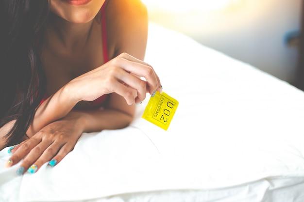 Dorosła seksowna kobieta przygotowuje i trzyma prezerwatywę w ciemnoczerwonej koronkowej bieliźnie damskiej bielizny na łóżku