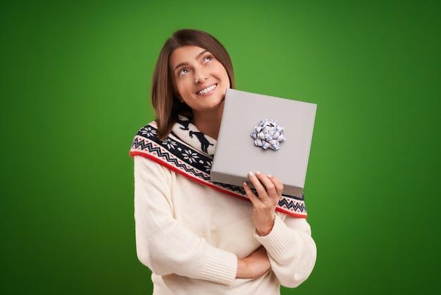 Dorosła szczęśliwa kobieta z prezentem świątecznym na zielonym tle