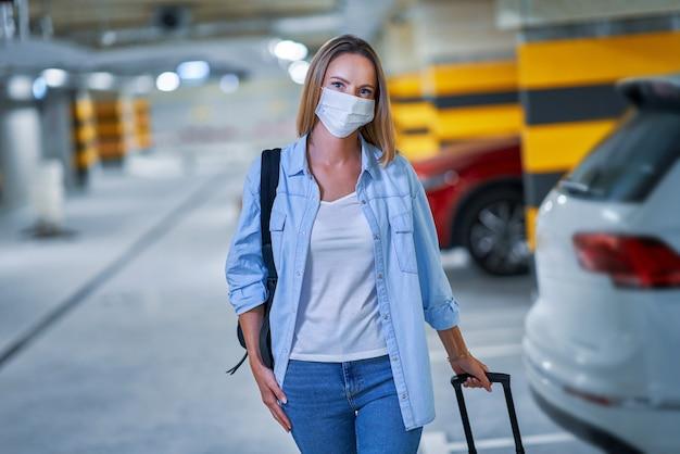 Dorosła turystka nosząca maskę z powodu procedur covid-19 na podziemnym parkingu lotniska