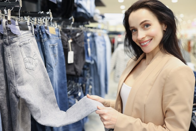Dorosła uśmiechnięta dziewczyna kupuje spodnie w sklepie odzieżowym