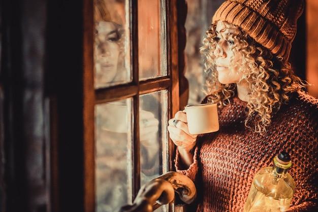 Dorosła zamyślona kobieta wygląda za oknem picia kawy w domu. kobiety odbite na szkle patrząc na zewnątrz, czekając i myśląc. koncepcja stylu życia w sezonie zimowym