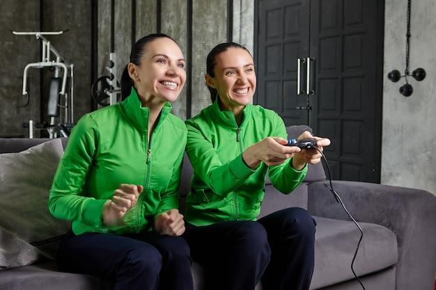 Dorosłe kobiety grają w gry wideo za pomocą joysticka z konsoli do gier