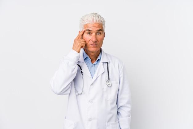 Dorośleć caucasian lekarki mężczyzna wskazuje świątynię z palcem, myśleć, skupiający się na zadaniu