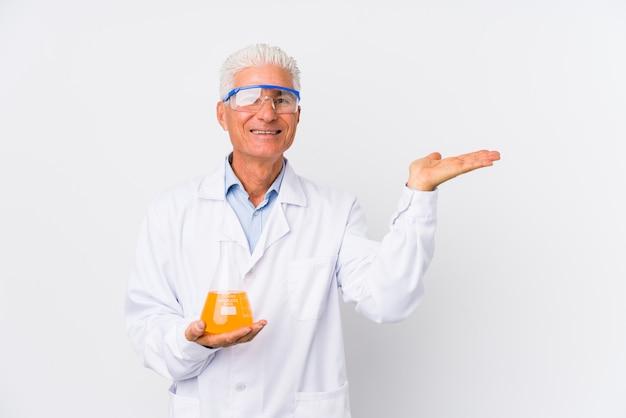 Dorośleć chemicznego mężczyzna odizolowywającego pokazywać odbitkową przestrzeń na palmie i trzymać inną rękę na talii.