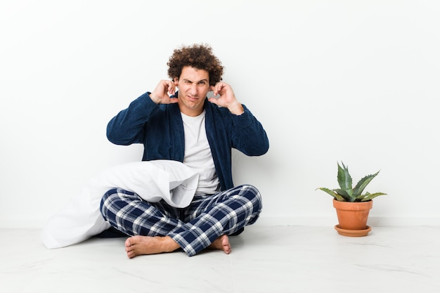 Dorośleć mężczyzna jest ubranym piżamę siedzi na domowej podłoga zakrywającym ucho z rękami.