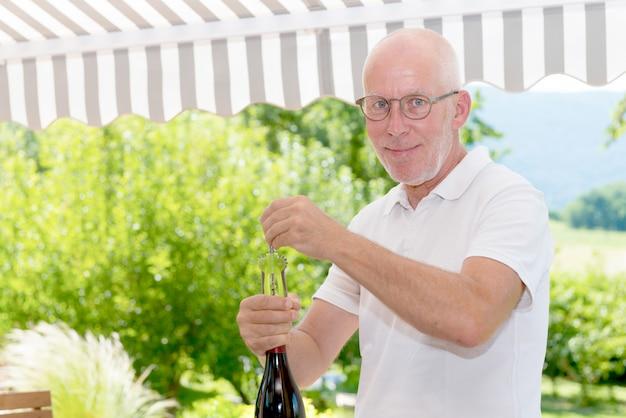 Dorośleć mężczyzna otwiera butelkę czerwone wino
