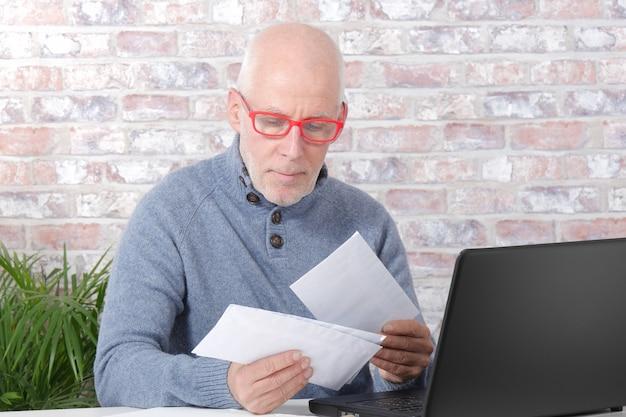 Dorośleć mężczyzna otwiera listową kopertę
