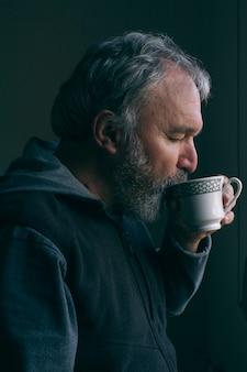 Dorośleć mężczyzna pije filiżankę kawy