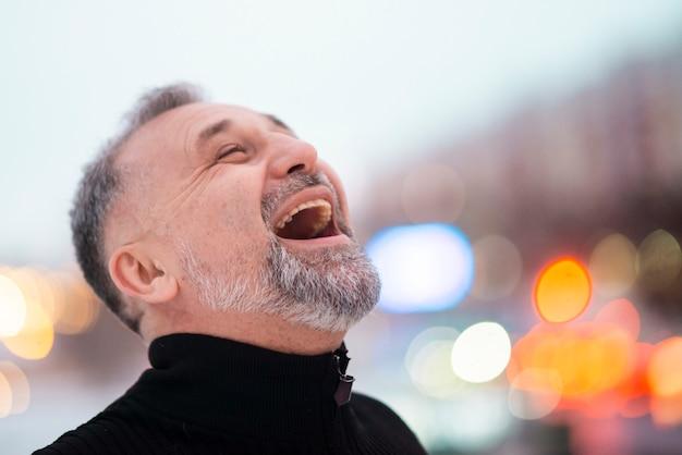 Dorośleć mężczyzna śmia się na zewnątrz zakończenia