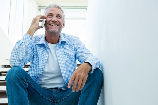 Dorośleć mężczyzna używa telefon komórkowego na krokach