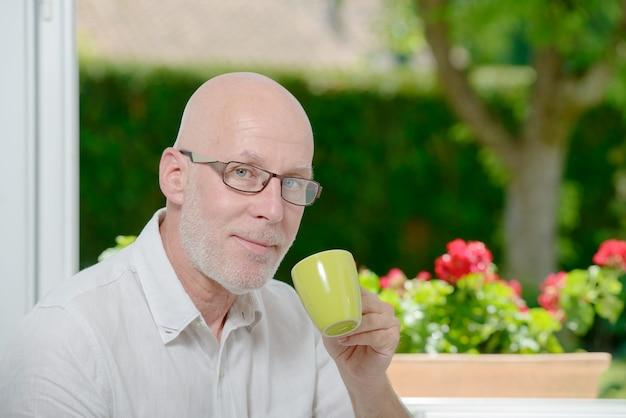 Dorośleć mężczyzna w domu z filiżanką kawy