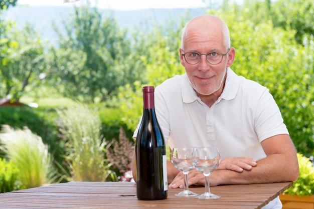 Dorośleć mężczyzna z butelką czerwonego wina, na tarasie