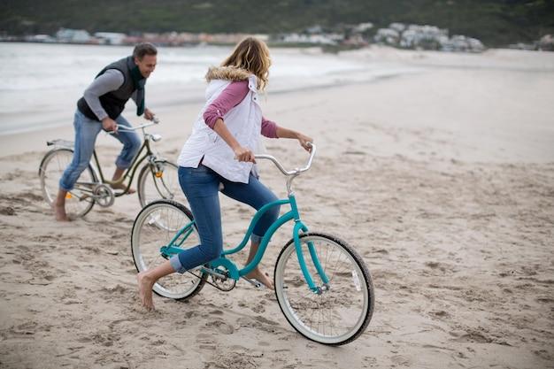 Dorośleć pary jeździeckich bicykle na plaży