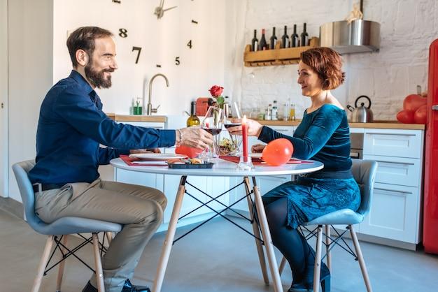 Dorośleć pary ma romantyczną kolację w domu na walentynka i robi grzance z czerwonym winem