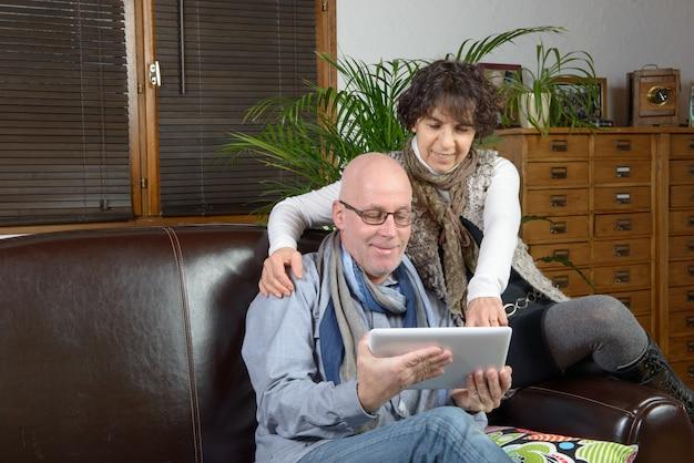 Dorośleć pary patrzeje cyfrową pastylkę