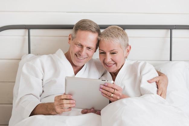 Dorośleć pary patrzeje na pastylce w łóżku