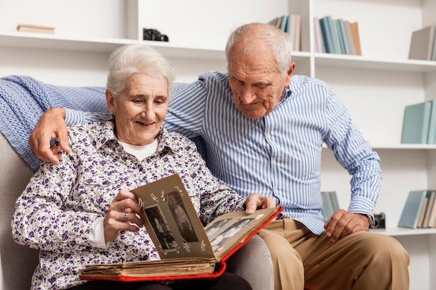 Dorośleć pary patrzeje w album fotograficznego
