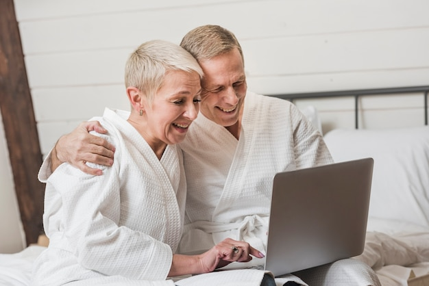 Dorośleć pary patrzeje wpólnie na ich laptopie w domu